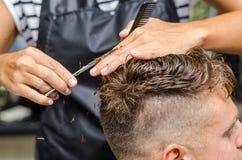 Men& x27; el corte del pelo de s scissors en un salón de belleza Imagen de archivo libre de regalías