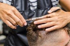 Men& x27; el corte del pelo de s scissors en un salón de belleza Imagenes de archivo