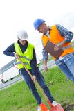 2 men employees digging hole in grass. 2 men employees digging a hole in the grass stock image