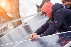 Men are engaged in the installation of solar cells. In the winter. Snow is falling down Stock Photos