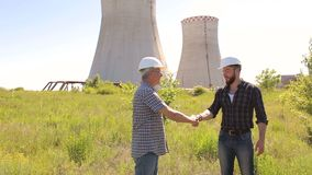 Men engineers shaking hands at construction site. Two male architects shaking hands at construction site. Two men engineers shaking hands on a background of stock video footage