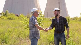 Men engineers shaking hands at construction site. Two male architects shaking hands at construction site. Two men engineers shaking hands on a background of stock footage