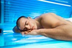 Men enjoying in solarium. Young man enjoying in solarium Royalty Free Stock Image