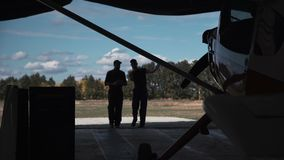 Men entering hangar. Two men entering hangar, looking at plane and talking with each other stock video footage