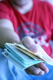 A men with euros. A men in the red t-shirt give 1500 euros in the hand Royalty Free Stock Photos