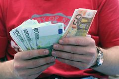 A men with euros. A men in the red t-shirt give 1500 euros in the hand Stock Photos