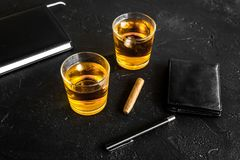 Men evening in bar with whiskey, cigar, wallet and notebook on black background Stock Photos