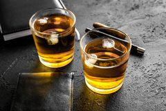 Men evening in bar with whiskey, cigar, wallet and notebook on black background Stock Photography