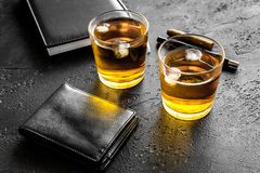 Men evening in bar with whiskey, cigar, wallet and notebook on black background Royalty Free Stock Photos