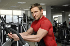 Men exercising. Handsome man exercising in the gym Stock Images