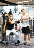 Men exercising on gym machine Royalty Free Stock Photos
