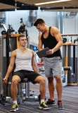Men exercising on gym machine Royalty Free Stock Photos