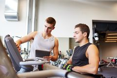 Men exercising on gym machine Royalty Free Stock Photo