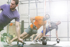 Men exercising with kettlebells in crossfit gym Stock Images