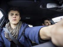 Men exploring car together sitting inside stock image