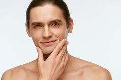 Men Face Care. Man Touching Smooth Skin After Shaving. On White Background. High Resolution stock photography