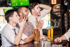Men fans watching football on TV and drink beer. Three other men Stock Photos