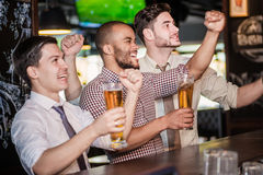 Men fans waving their hands and watching football on TV and drin Stock Image
