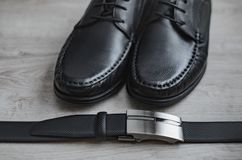 Men fashion. Men accessories. Black shoes and black belt . Still life. Business look on a wooden background.  stock photo