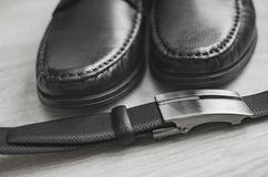 Men fashion. Men accessories. Black shoes and black belt . Still life. Business look on a wooden background royalty free stock photo