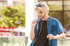 Hipster man standing on city street listening music. Men fashion, technology, urban style clothing concept. Hipster guy standing on city street wearing jeans Royalty Free Stock Image