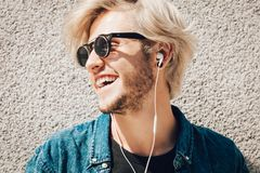 Hipster man standing on city street listening music. Men fashion, technology, urban style clothing concept. Hipster smiling guy standing on city street wearing Stock Image