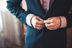 Men fastens his black suit Stock Photo