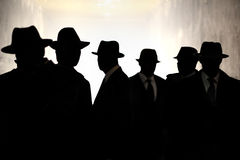 Men in fedora hats silhouette. Security, Privacy, Surveillance Concept. Several men in suits and hats in silhouette. Concept for security, privacy and stock images