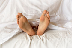 Men feet alone in a bed. Under white sheets Royalty Free Stock Photos