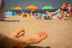 Men feet on the beach. In the background sunbathers with umbrellas and windbreaks Stock Photos