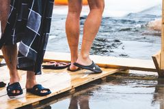 Men feet on dais in front of ice-hole. Men bare feet on the wooden platform in front of an ice-hole in a frozen pond in the winter feast of Epiphany Royalty Free Stock Photo
