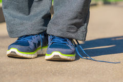 Men feet in sneakers and untied lace Royalty Free Stock Photography