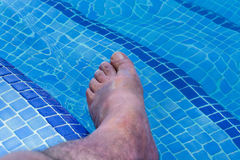 Men feet in a swimming pool Stock Images