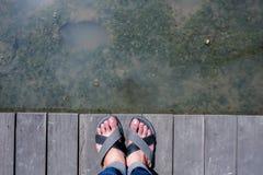 Men feet on the wooden bridge royalty free stock photography