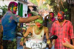 Men at the festival of   colors India. The man on nthe moped at the festival of colors India Royalty Free Stock Photo