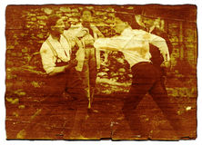Men fighting - on wood. This is a digital remake of an antique photo taken in the north of Italy in 1920.The old photo is put on a cherry wood texture.Two men stock photo