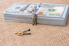 Men figurines beside the bundle of US dollar banknote Stock Image
