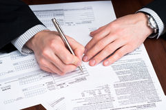 Men filling out documents on a desk. royalty free stock photography