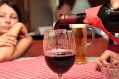 The men fills red wine. In restaurant Stock Image
