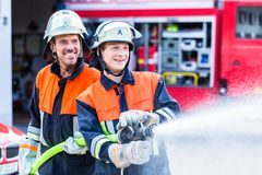 Men of the fire department extinguish fire. Fire fighters from fire brigade extinguish fire stock image