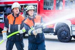Men of the fire department extinguish fire. Men of the fire brigade extinguish fire stock photos