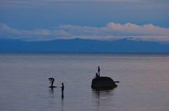 Men fish from rocks on Lake Malawi Stock Photos