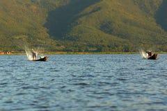 Men fishing on boat on Inle lake in Burma stock photo