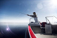 Men is fishing at the boat. In sunny day Royalty Free Stock Photo
