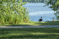 Men fishing with is dog at Andre Corbeil Park Stock Image