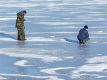 Men fishing at frozen lake. Ice drill visible. Smudges of snow Stock Images