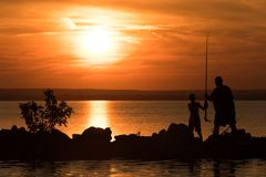 Men fishing with his son. Joint family program at the lake. In a hot summer day the father teach to fishing his son Stock Images