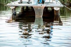 Men fishing on the lake. Fishing net on the wooden pier, men fishing on the lake, cropped image royalty free stock photo