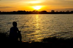 Silhouette angler. Men are fishing by the lake royalty free stock photos