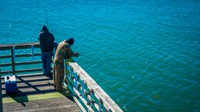 Men fishing on a pier at the coast royalty free stock photos